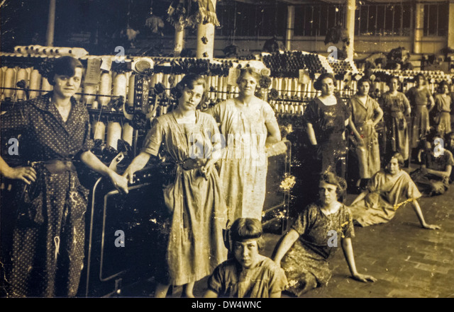 Old archival photograph showing female workers posing in spinning mill in the early twentieth century, Ghent, Belgium - Stock Image