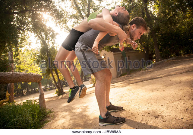 Man and woman exercising outdoors, back to back, man stretching woman over back - Stock-Bilder