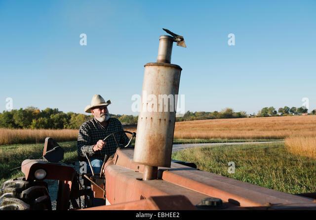 Senior male farmer driving tractor on rural road, Plattsburg, Missouri, USA - Stock Image