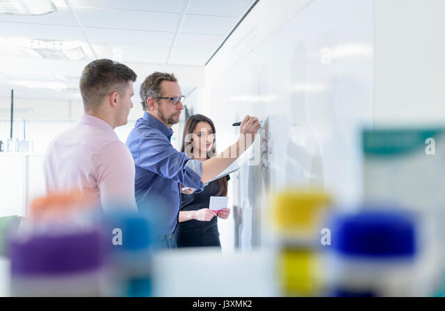 Pharmacists using whiteboard in meeting in pharmaceutical factory - Stock Image