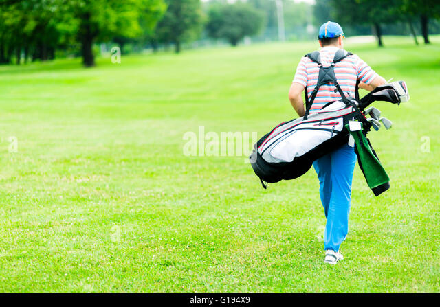 Golfer carrying his equipment on a beautiful sunny day - Stock Image