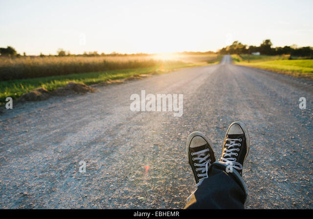 Feet of farmer traveling on rural road at dusk, Plattsburg, Missouri, USA - Stock Image