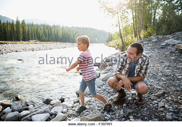 Father and son throwing stones at craggy riverside - Stock Image