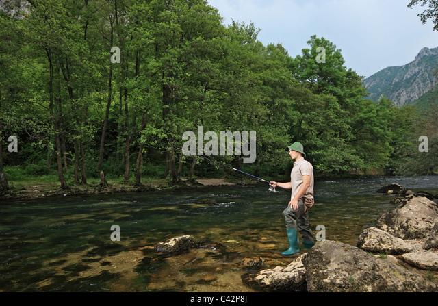 A young fisherman fishing on a river with trees in the background - Stock Image