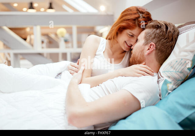 Beautiful couple in love awake  in bed and smiling - Stock Image