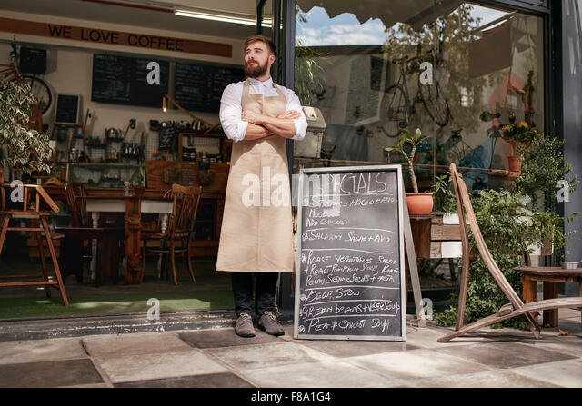 Full length shoot of a young waiter standing in door of a cafe. Young man with beard wearing an apron  standing - Stock Image