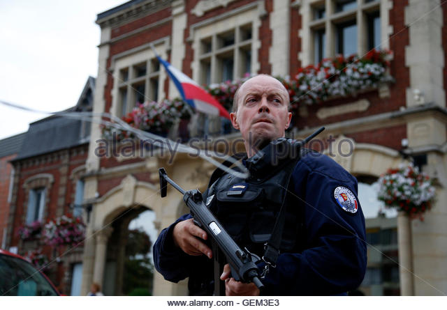 A policeman secures a position in front of the city hall after two assailants had taken five people hostage in the - Stock-Bilder