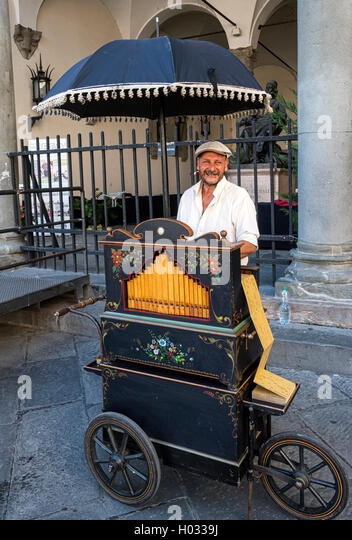 Busker plays a barrel organ in Piazza San Michele, Lucca, Tuscany, Italy - Stock Image