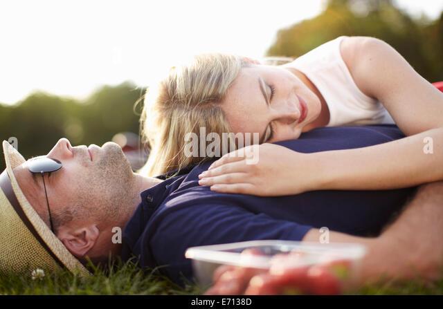 Couple lying asleep in park - Stock-Bilder