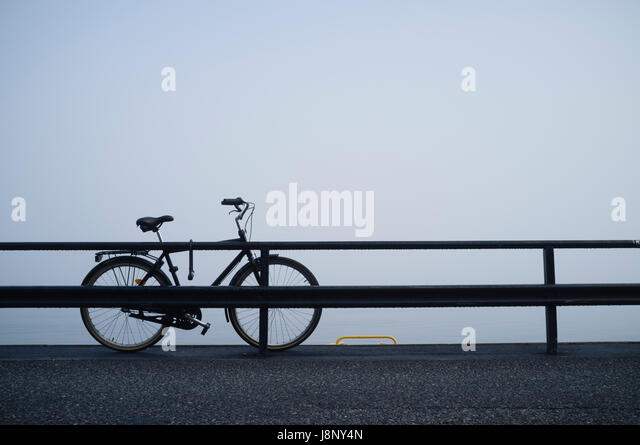Abandoned bicycle behind railing - Stock-Bilder