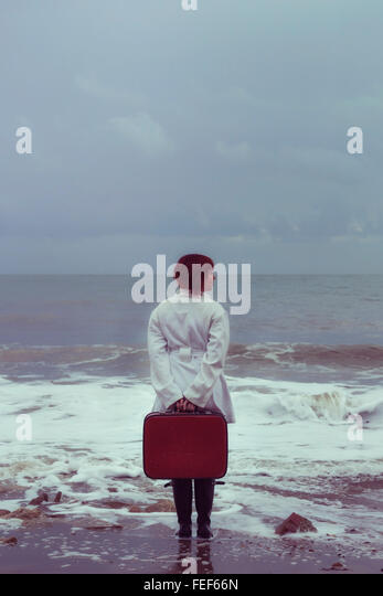 a woman in a white coat with a red suitcase at the sea in winter - Stock Image