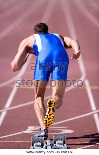 Male athlete by starting blocks, rear view - Stock Image