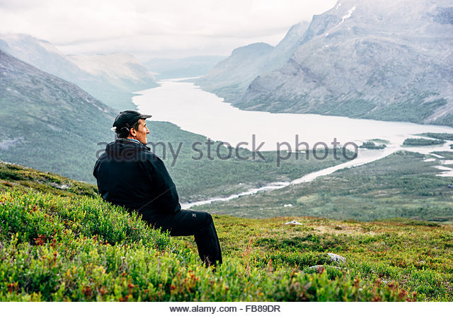 Sweden, Lapland, Kaitumjaure, Kungsleden, Male hiker sitting and looking at river in mountain valley - Stock Image