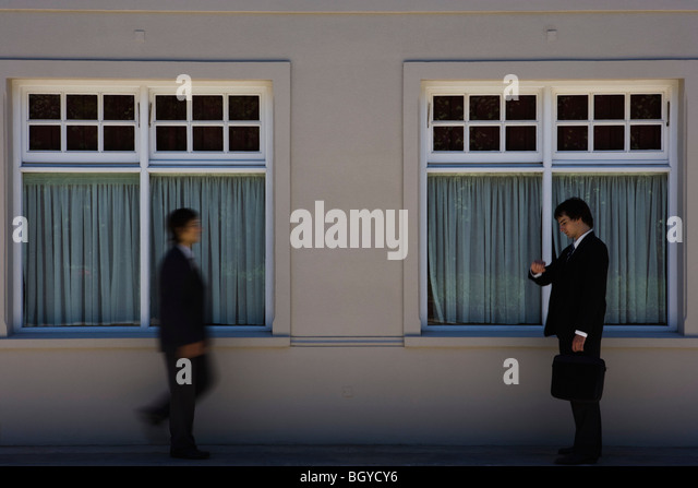 Young businessman standing on sidewalk, checking time as another man approaches - Stock-Bilder