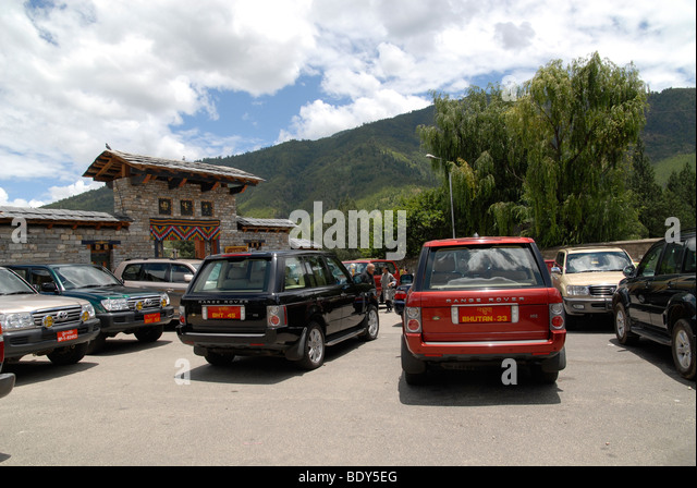 Official cars of the government of Bhutan in front of the memorial chorten of the third king, Thimphu, Bhutan - Stock Image
