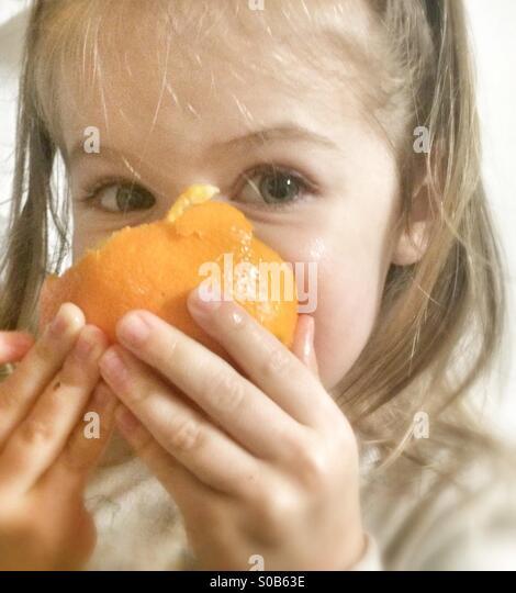 Toddler Eats Orange - Stock Image