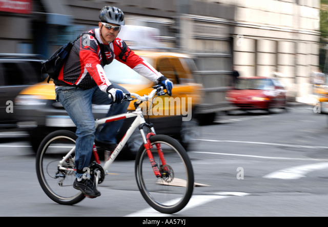 Young male bike messenger in traffic in New York City Stock Photo