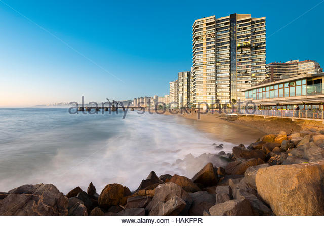 View of rocks and surf on Acapulco Beach with Muelle Vergara in luxury resort town of Vina del Mar, Valparaiso Region, - Stock Image