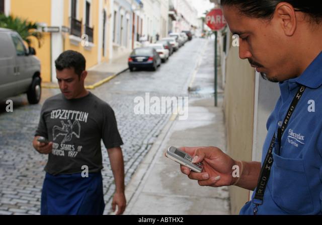 Puerto Rico Old San Juan Calle de la Cruz Hispanic men cell phones - Stock Image