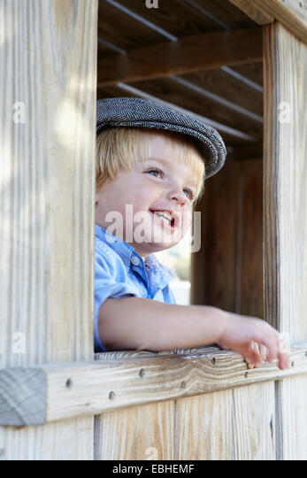 Male toddler in flat cap leaning out of shed window - Stock Image