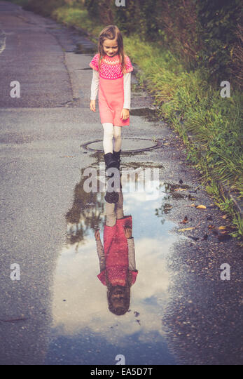 Little girl looking at her mirror image on a puddle - Stock-Bilder