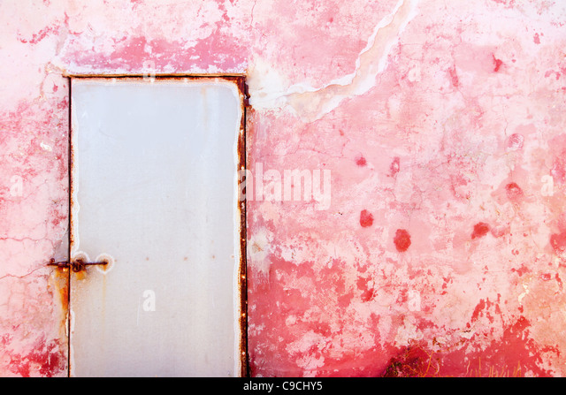 Pink mediterranean grunge door and wall with weathered texture - Stock Image