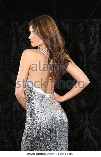 Three quarter shot of a beautiful young woman in a silver sequined backless dress looking away hand on hip on a - Stock Image