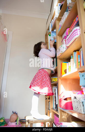 Young girl standing on chair to reach book on bookshelf - Stock Image