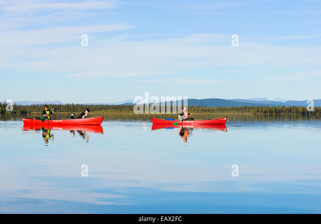 Two people canoe on a quiet lake - Stock Image