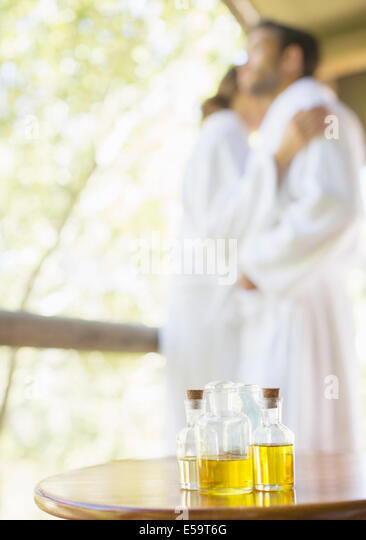 Bottles of massage oil on side table - Stock Image