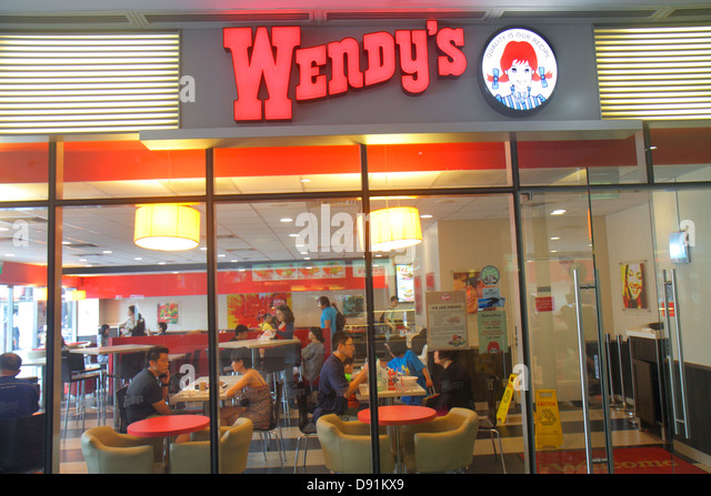 Singapore Kallang Road Wendy's fast food restaurant front entrance Asian man woman - Stock Image