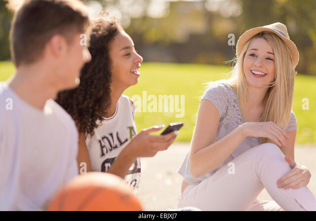 Three young adult basketball players chatting and laughing - Stock Image