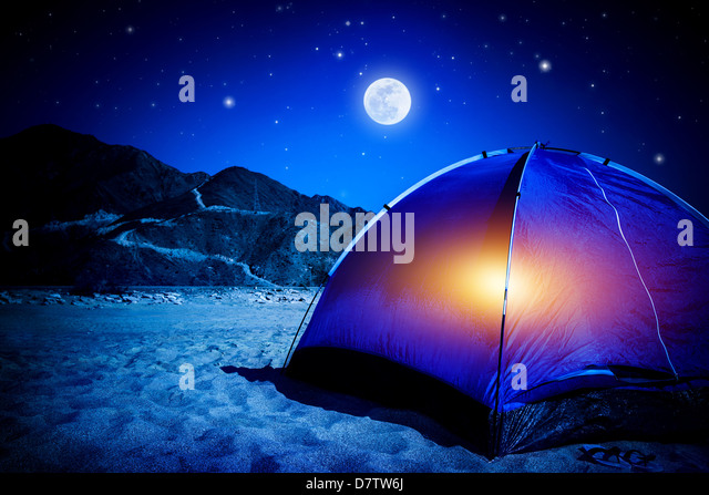 Camp on sandy beach, tent at the night with light inside, moon light, active tourism, hiking and traveling concept - Stock Image