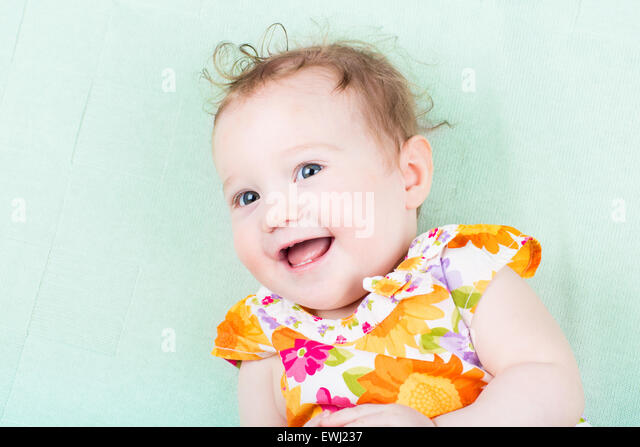 Funny laughing baby girl in a colorful dress on a purple blanket - Stock Image