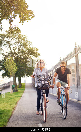 Romantic couple cycling along a cycle path in an urban park holding hands and smiling at the camera on a hot summer - Stock Image