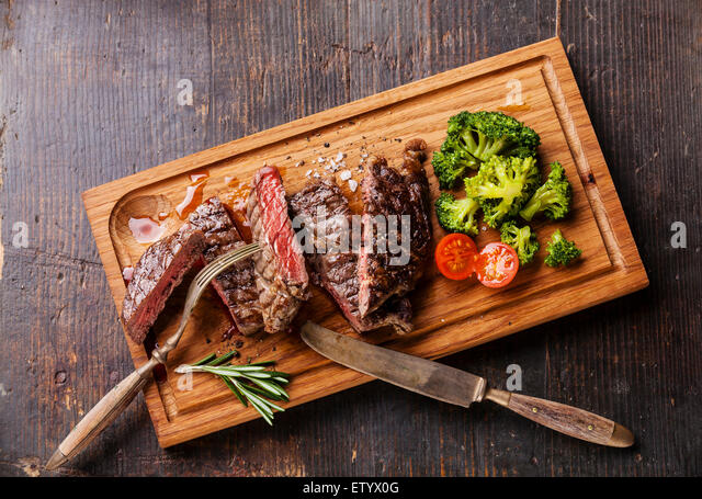 Sliced medium rare grilled Beef steak Ribeye with broccoli on cutting board on wooden background - Stock Image