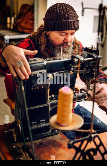 Male worker sewing bag pocket in workshop - Stock Image