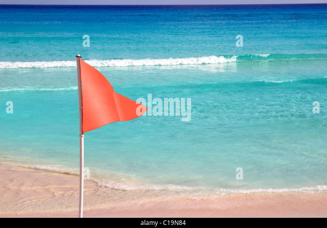 dangerous red flag in beach rough sea signal - Stock Image