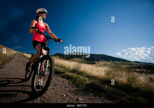 A female mountain biker stops to enjoy the view while riding the trails of Mt. Sentinel, Missoula, Montana. - Stock Image