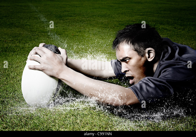 Rugby player on wet field - Stock Image