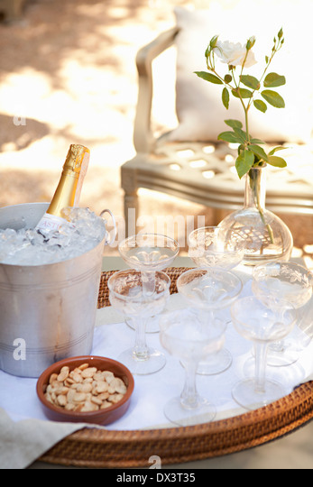 Champagne bottle chilling in silver ice bucket on tray with champagne glasses and marcona almonds on sunny patio, - Stock Image