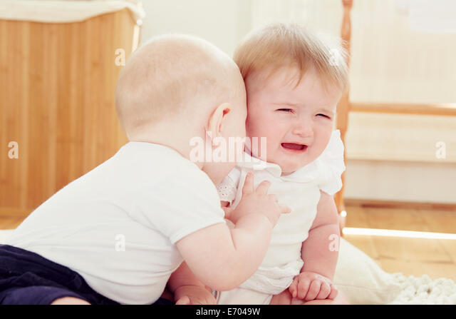 Crying baby girl with baby boy leaning toward her - Stock Image
