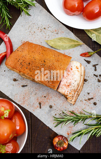 A large piece of bacon baked with spices and herbs on a paper with marinated tomatoes. The top view. A festive meal. - Stock Image