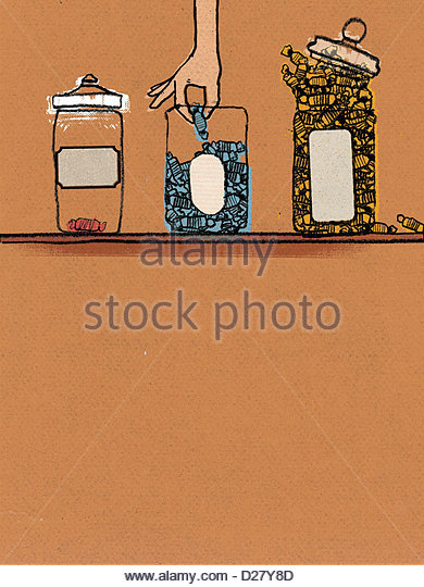 Hand reaching for candy in jar - Stock Image