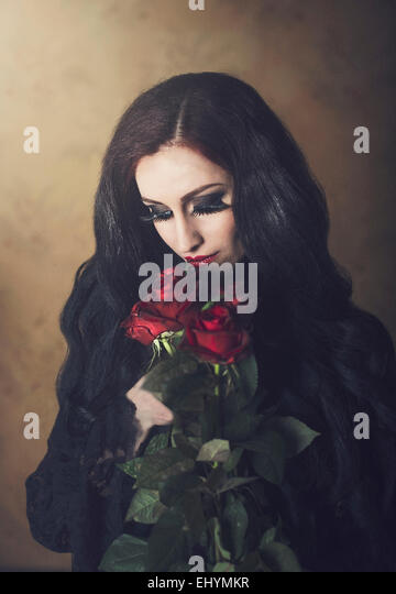 Portrait of a woman in black holding bunch of red roses - Stock-Bilder