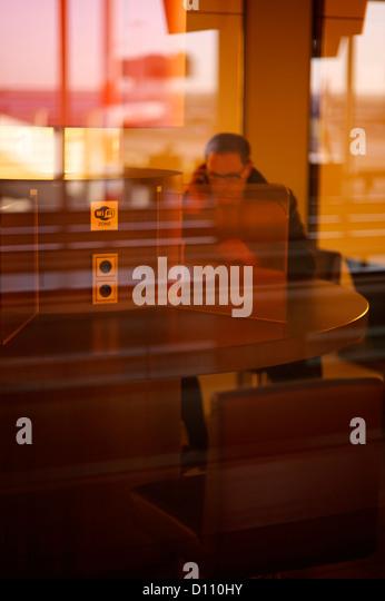Man sitting behind glass wall in an international airport - Stock-Bilder