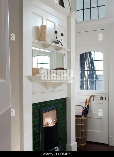 White entrance hall with green fireplace, Edwardian residential house, Kingsmead, UK - Stock Image