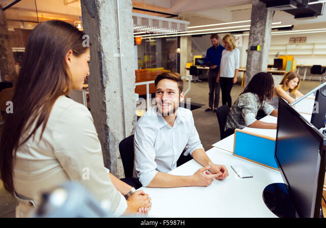 People working at busy modern office in front of computers - Stock Image