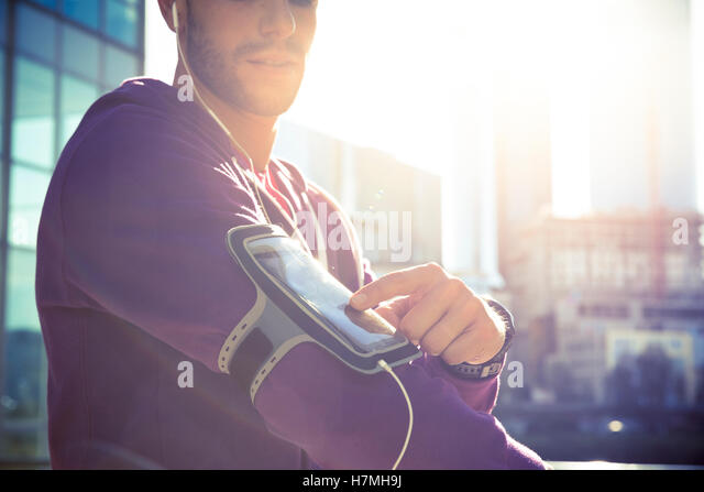 Running workout man listening to music with mp3 player armband or smart mobile phone. - Stock Image
