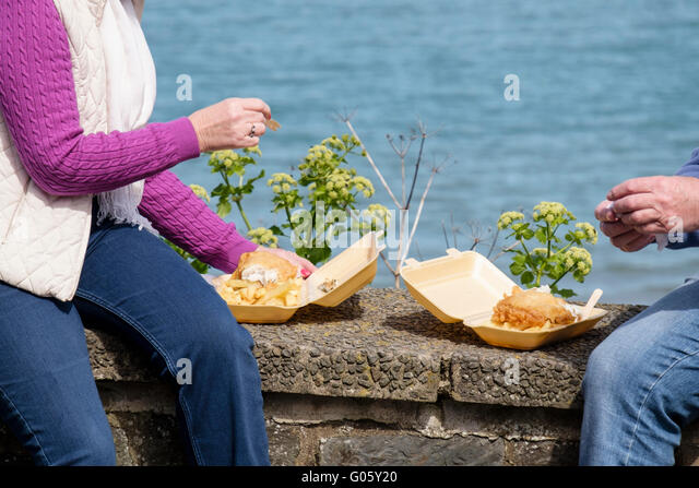 Two holiday makers sitting on a sea wall eating fish and chips from polystyrene containers in seaside town of New - Stock-Bilder